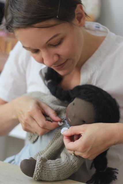 Über die Autorin: Maike knöpft einer Puppe mit schokobrauner Haut die beige Strickjacke zu