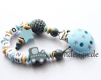 hellblau-graue Schnullerkette mit Häkelperle, Stern, verschiedenen Perlen, bedrucktem Clip und einer Perle in Holzeisenbahn-Form
