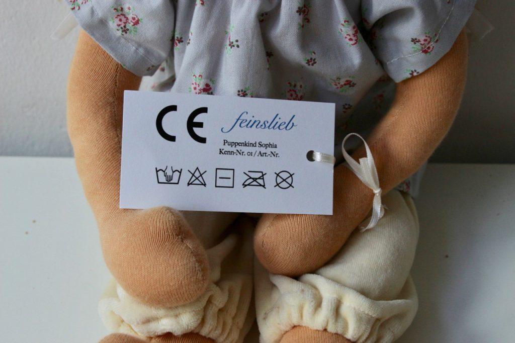 Oberkörper einer Puppe, die am Arm ein Etikett mit CE-Kennzeichnung und Wäschesymbolen hat