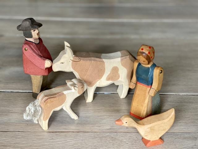 CE-Kennzeichnung Holzspielzeug: Holzfiguren auf Holztisch: Bauer, Kuh, Kälbchen, Bäuerin und Gans von Ostheimer.